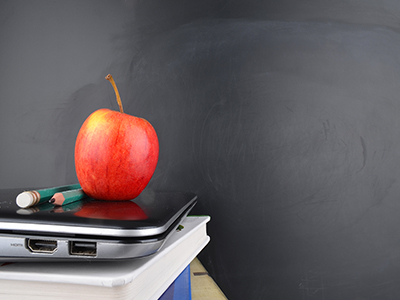 Pile of apple, pencils, laptop and book against black chalkboard
