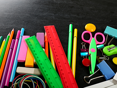 Neon-colored school supplies on black background