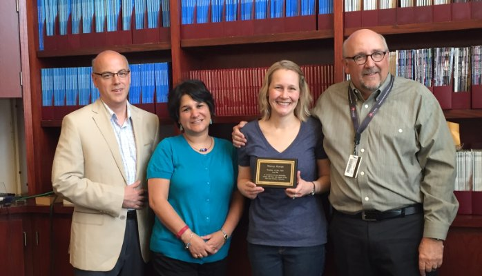PAC representatives surprised Dr. Moran at her lab meeting on May 31st to give her the award. Left to Right: PAC members Jeff Agnoli and J. Marcela Hernandez, Nancy E. Moran, and Steven Clinton